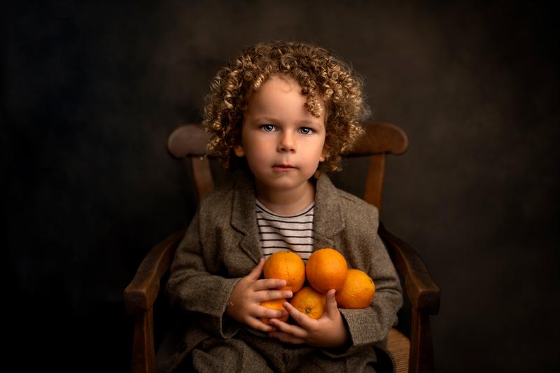 Petit garçon bouclé aux yeux bleus portant des oranges