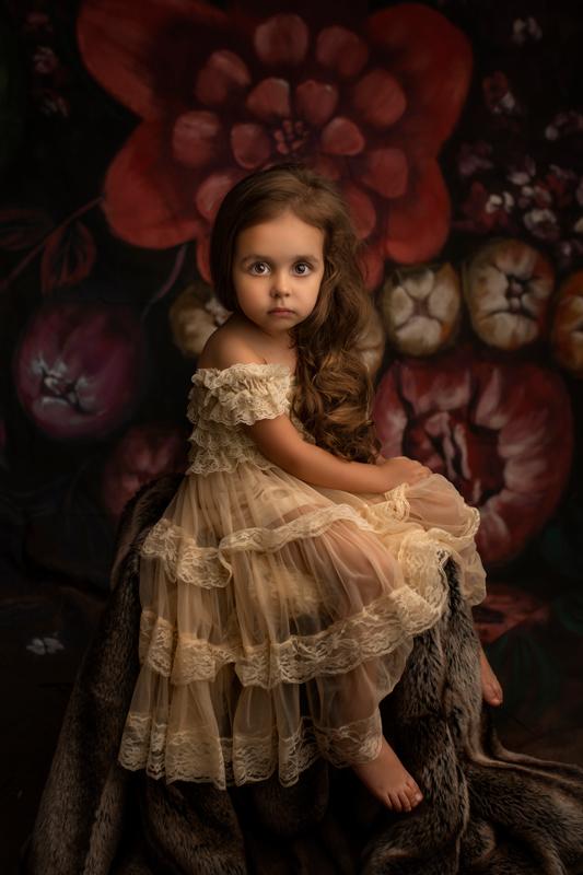 Petite fille au regard intense robe dentelle posant dans un décor fleuri
